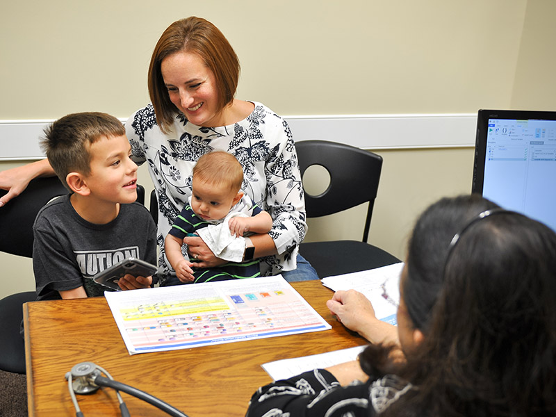 Mom with young ADHD son and baby in Dr. Sheila Woods office at Greenville ADHD Specialists